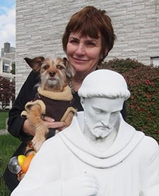 Attendee at Blessing of the Animals event poses with her dog next to statue of St. Francis