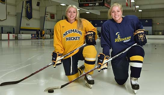 Photo of twin sisters Jillian and Halle Crane posing in their ice hockey uniforms on the ice.