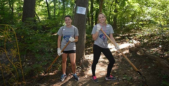 Two NU students help clear the trail at Providence Animal Center
