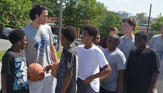 First-year Knights giving some basketball tips to a group of Nativity Prep students