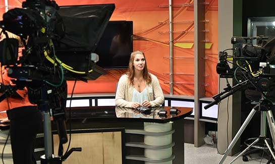 Photo of Melanie Hart, a student at Interboro High School, settling in behind the news desk and while waiting for her cue to begin the next story.