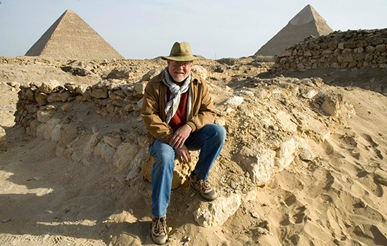 Presenter Dr. Stephen Phillips is shown seated in front of two Egyptian pyramids.