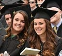 Two smiling female graduates in cap & gown