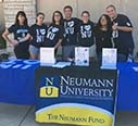 Group of students manning The Neumann Fund info table