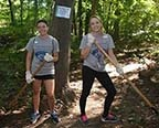 Two female students doing yardwork for community service